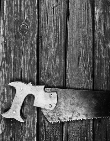 saws: Old rusty saw on wooden background, bw photo Stock Photo