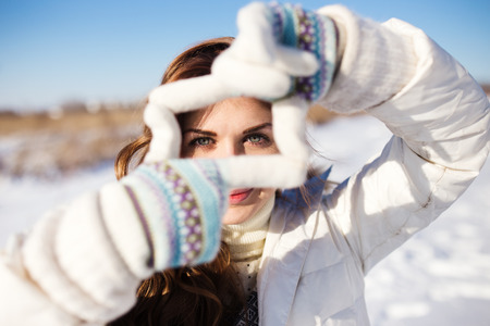having fun in winter time: Pretty girl having fun outdoor, making frame with hands, taking picture with imaginary camera, winter time Stock Photo