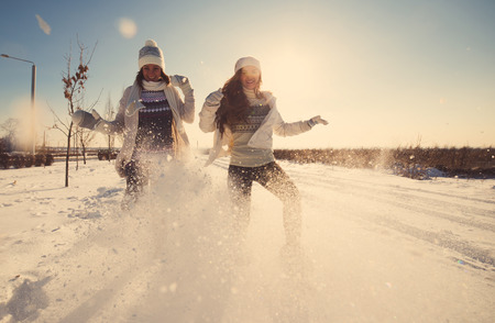 snow day: Two girlfriends have fun and enjoy fresh snow at beautiful winter day