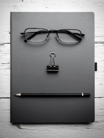 Notepad, eyeglasses, paperclip and pencil on wooden table. Black and white photo. photo