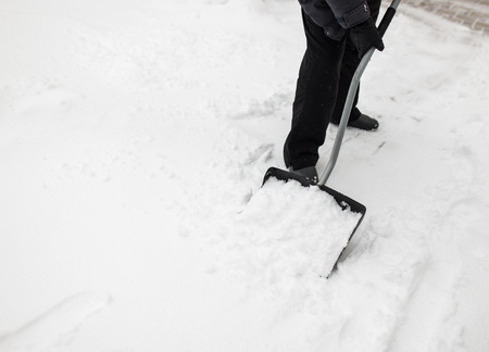 sidewalks: Man with snow shovel cleans sidewalks in winter Stock Photo