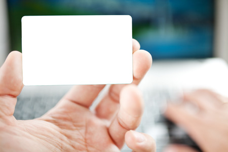 cvv: Closeup of a man shopping online using laptop with credit card. Credit card is blank. Credit card template