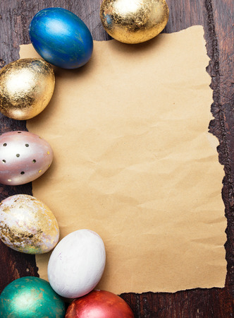 Easter eggs on wooden table with blank paper for text. Holiday background photo