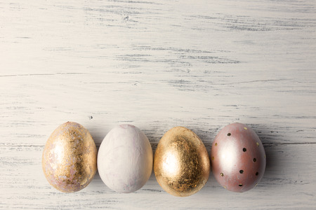 gold egg: Easter eggs on wooden table. Holiday background