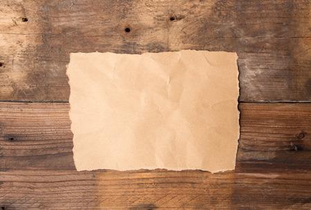 Piece of torn paper on old grunge wooden table Standard-Bild