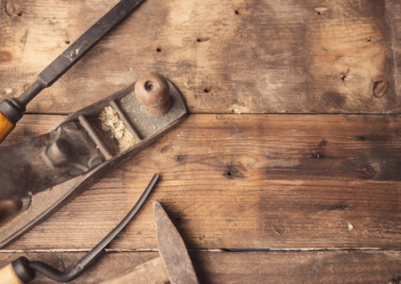 Od vintage hand tools on wooden background. Carpenter workplace.  Tinted photo Banco de Imagens