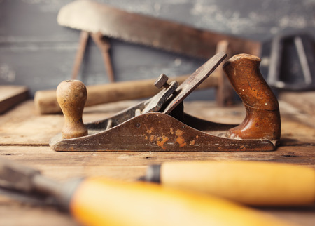 workbench: Od vintage hand tools on wooden background. Focus on jack-plane. Carpenter workplace. Tinted photo Stock Photo