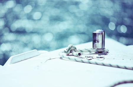 ancla: Blanco cuerda de amarre atado alrededor de anclaje de acero en el barco o nave, azul tintado