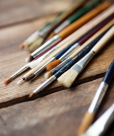 art supplies: Paintbrushes on a wood background,