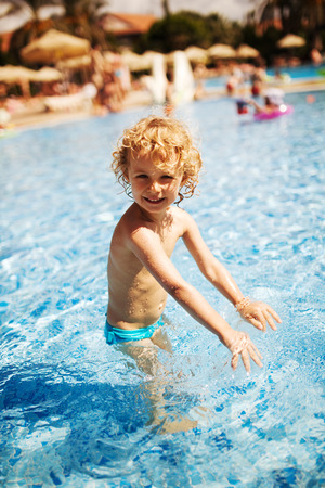 arm bands: Little girl in swimming pool. Summer outdoor.