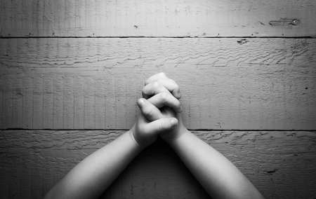 Childs hands folded together in prayer. Black and white photo