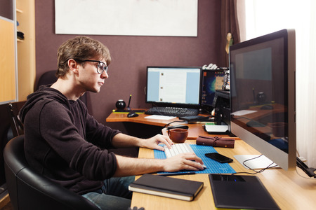 Freelance developer and designer working at home, man using desktop computer. Stock Photo