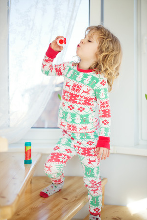 blowing bubbles: Cute little girl blowing bubbles at home