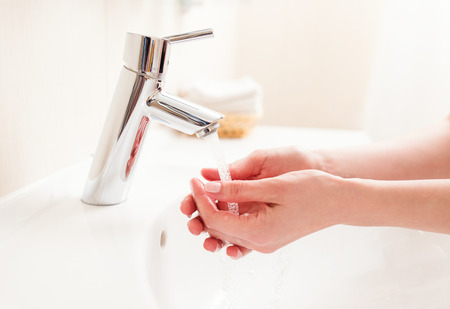Washing of hands in bathroom, close up photo