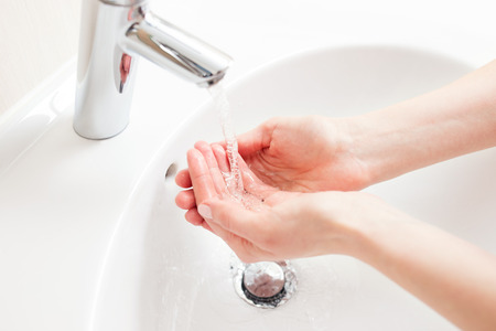 cleaning bathroom: Washing of hands in bathroom, close up photo