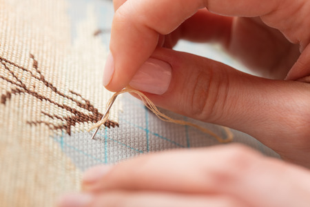 sewing cotton: Woman hands doing cross-stitch. A close up of embroidery. Stock Photo