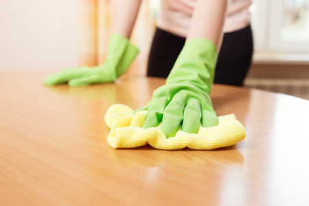 Woman cleaning stains off the table, close up photo Stock Photo
