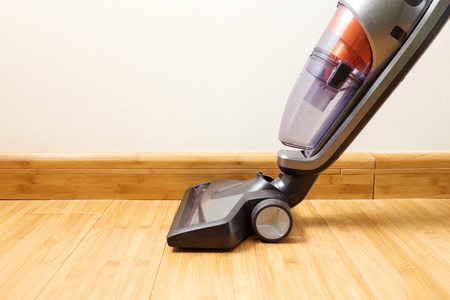 Cordless vertical vacuum cleaner cleaning parquet floor. Stock Photo