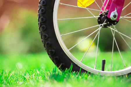 bicycle wheel: Childrens bicycle on green grass, close up photo Stock Photo