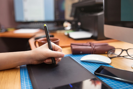 graphic tablet: Close-up of a mans hand with a pen stylus, drawing on a graphic tablet Stock Photo