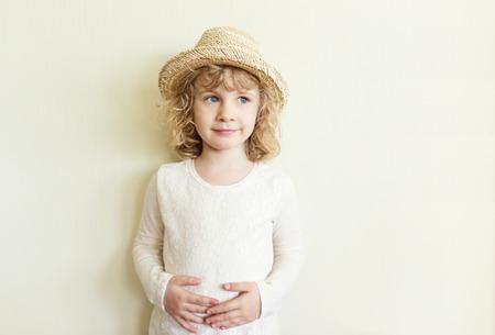 Cute little girl in straw hat standing near wall