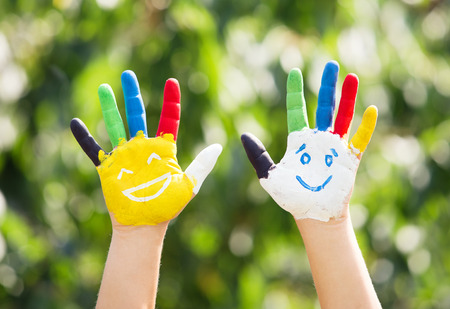 colorful paint: Colored hands with smile painted in colorful paints against green summer background. Lifestyle concept