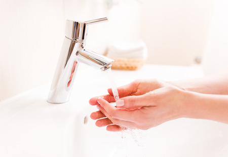 Woman washing your hands in bathroom
