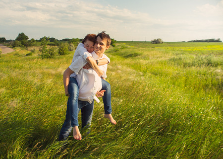 red grass: Happy couple standing in the field at the sunset, tinted photo Stock Photo
