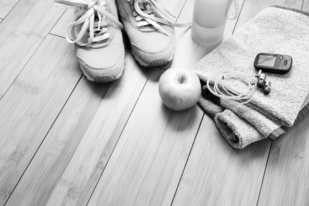 undone: Pair of sport shoes and fitness accessories. Fitness concept. Black and white photo