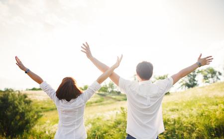 Pareja de pie en el campo de las manos en alto, verano al aire libre Foto de archivo - 41752660