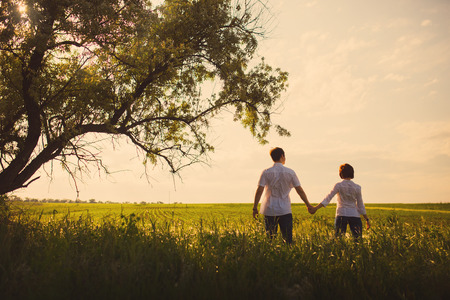 Happy couple standing in the field at the sunset, tinted photo Standard-Bild