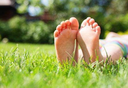 Pequeños pies en la hierba, cierre encima de la foto