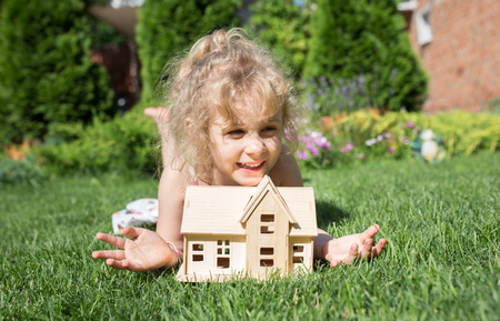 family outside: Portrait of little girl lying on grass with wooden model of house in hands,  summer outdoor, new home concept