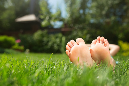 Little feet on the grass, close up photo Stock Photo