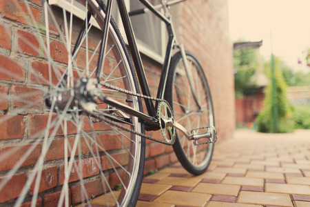 clavados: Vieja bicicleta singlespeed estilo contra la pared de ladrillo, foto teñida