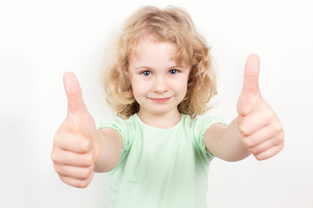 green thumb: Little girl with thumbs up on white background Stock Photo