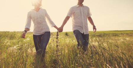 romance: Casal segurando as mãos que andam através de um prado, foto feliz matizado Imagens