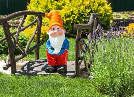lawn gnome: Wooden decorative bridge with garden dwarf  in home garden. Stock Photo