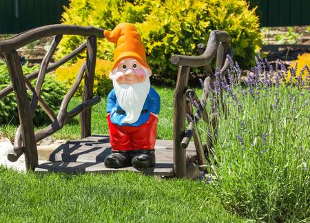 dwarves: Wooden decorative bridge with garden dwarf  in home garden. Stock Photo