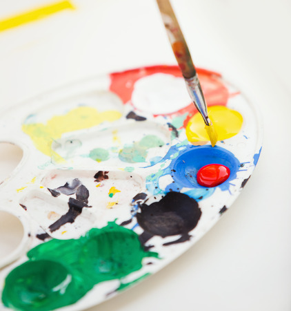 used: Plastic paint palette with paint and brush, close up photo