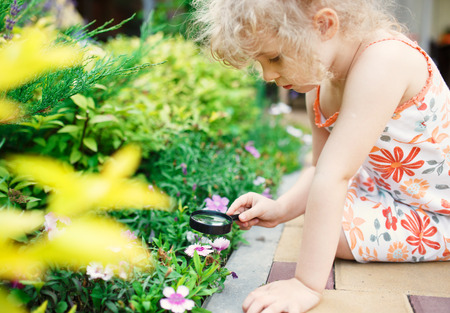 Little girl exploring nature with a magnifying glass Standard-Bild