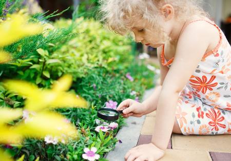 La niña explora la naturaleza con una lupa