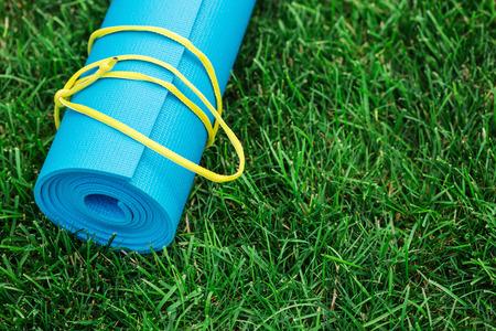 Blue yoga mat on green grass, close up photo, fitness concept