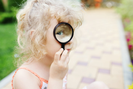 fields of flowers: Little girl looking through a magnifying glass Stock Photo
