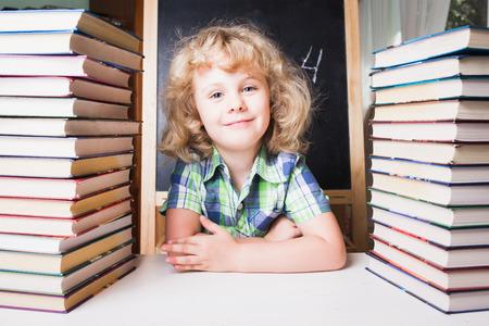 mignonne petite fille: Portrait de jolie fille intelligente souriant alors qu'il était assis avec pile de livres à table