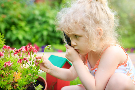 La niña explora la naturaleza con una lupa Foto de archivo