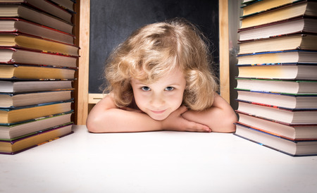 stacked books: Portrait of cute smart girl smiling while sitting with stack of books at table