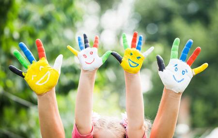 sonrisa: Manos de colores con la sonrisa pintada en pinturas de colores contra el fondo verde de verano. Concepto de estilo de vida