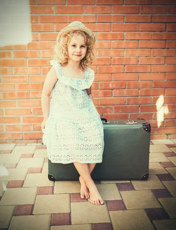 vintage photo: Little girl with vintage suitcase. Travel concept. Retro tinted photo