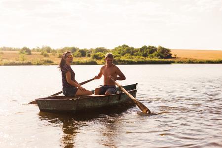 femme romantique: Heureux couple romantique ramer un bateau sur le lac.